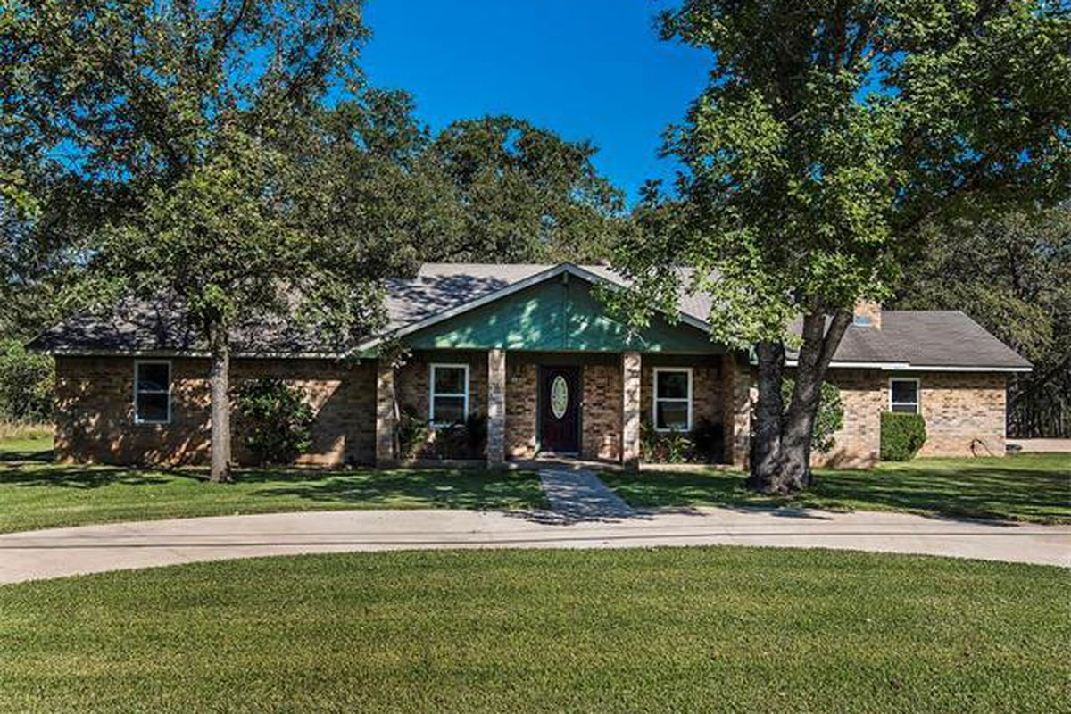 Older ranch-style brick home with blue peaked roof over porch