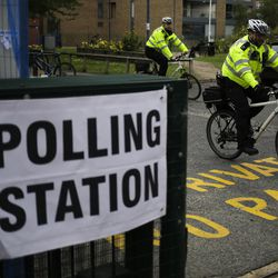 Police officers ride away on their bikes after inspecting the polling station for Britain's general election, at Bermondsey Village Hall in the London Bridge area of London, Thursday, June 8, 2017.