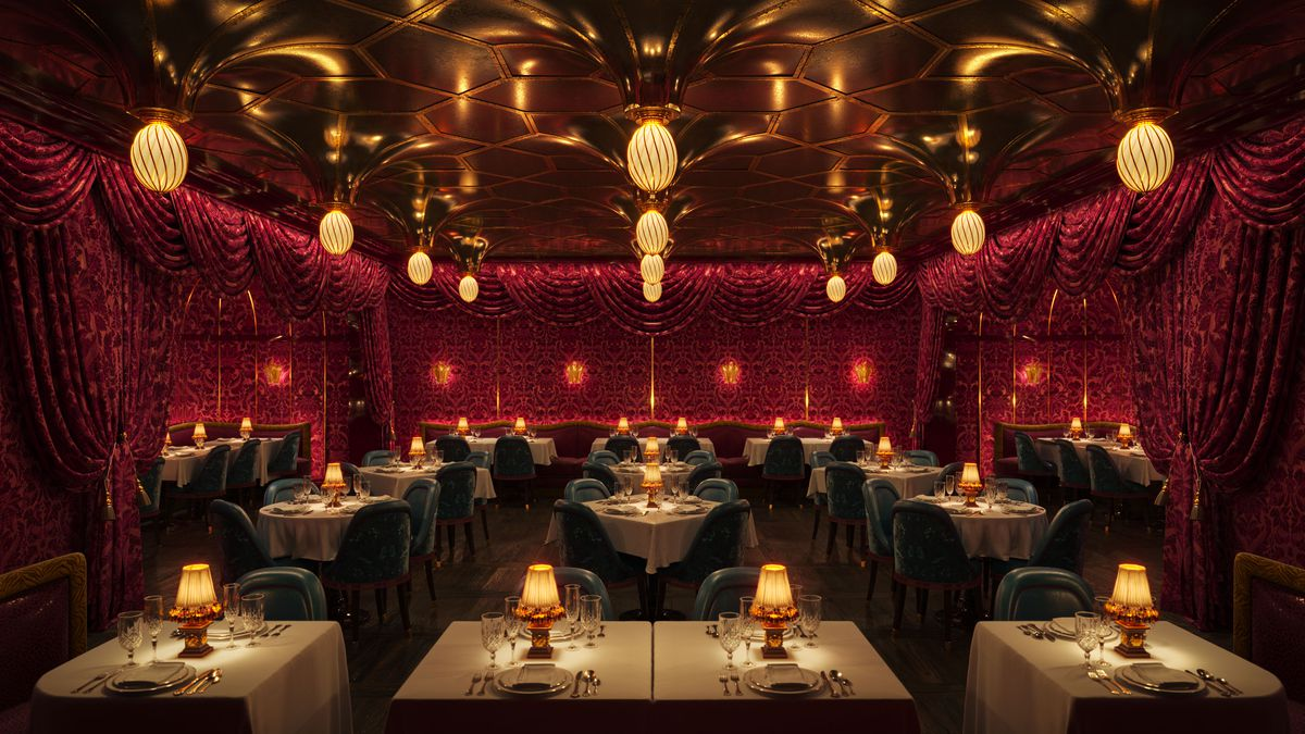 An ornate restaurant with white tablecloth seating, red velvet curtains, and custom brass light fixtures hanging from the ceilings
