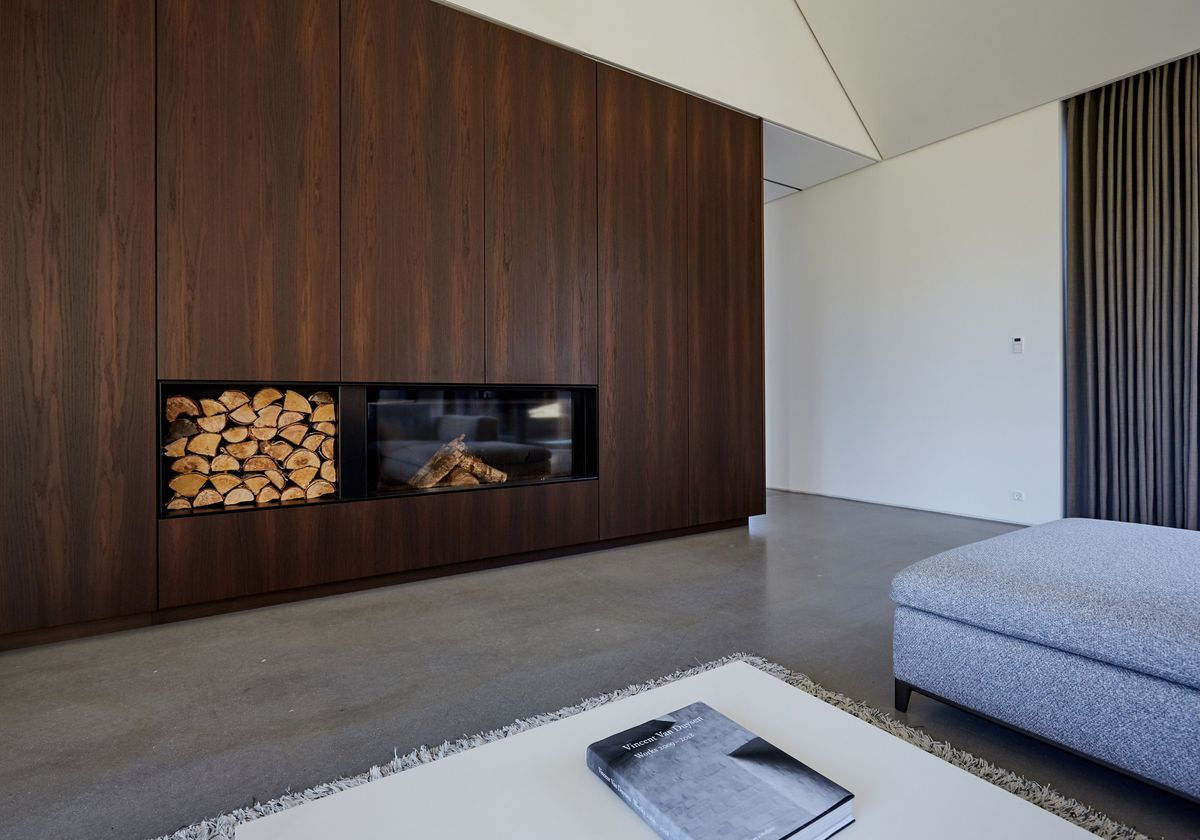 In the open living room, the gray sectional faces a full-height wooden wall of cabinetry, featuring a modern fireplace and firewood.