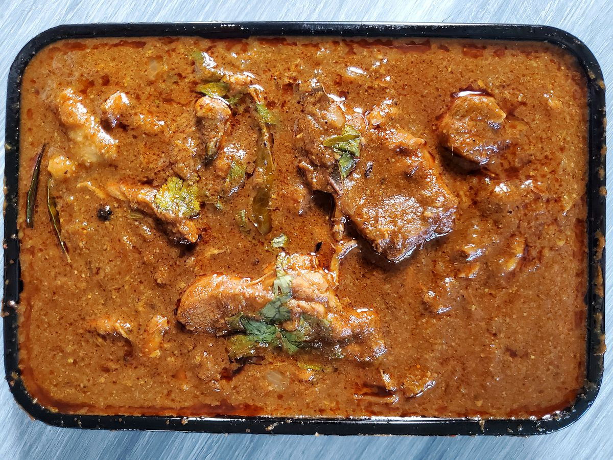 A brown stewed chicken kurunga dish sits in a black to-go container