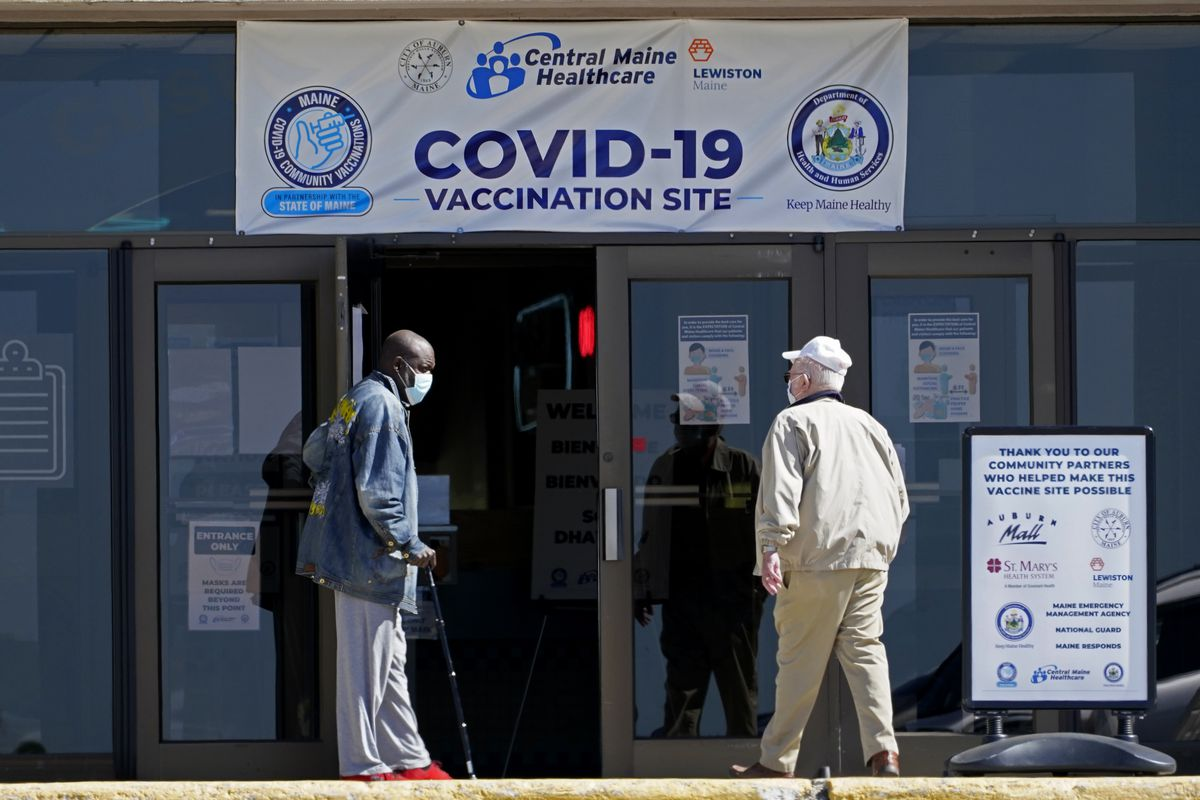 In this May 12, 2021, file photo, one man holds the door for another as they arrive at a COVID-19 vaccination clinic at the Auburn Mall in Auburn, Maine.