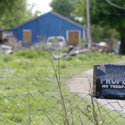 A no trespassing sign is posted outside the home of Jake England, 19, and Alvin Watts, 32, in Tulsa, Okla., Monday, April 9, 2012. England and Watts are suspects in the shooting rampage that left three people dead and terrorized Tulsa's African-American community.