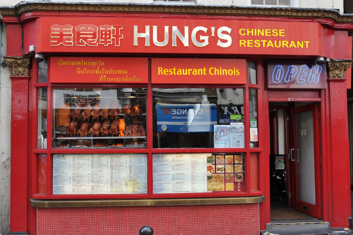 The exterior of Hung's restaurant on Wardour Street, Chinatown, London, painted red with roast ducks in the window