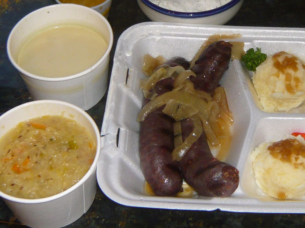 To-go containers of Polish food, including soup, sausage, and mashed potatoes
