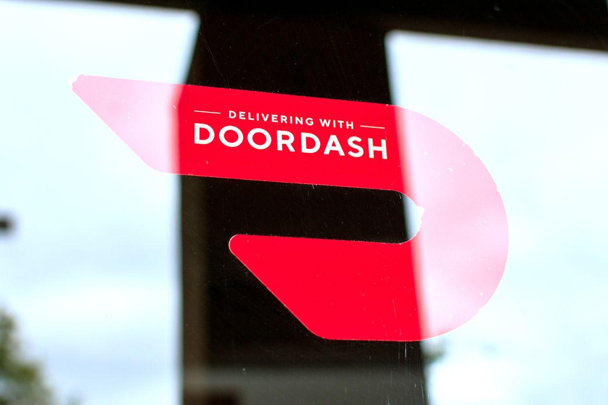 The red DoorDash logo emblazoned across the window of a restaurant