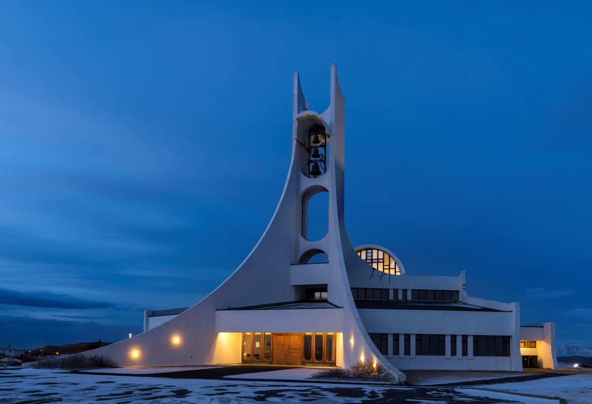 """The exterior of <span data-author=""""843"""">The Stykkisholmskirkja church in Iceland. The facade is white with a bell tower that slopes upward towards the sky.</span>"""