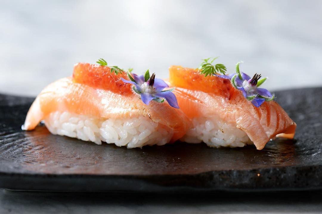 salmon belly nigiri garnished with citrus and edible flowers