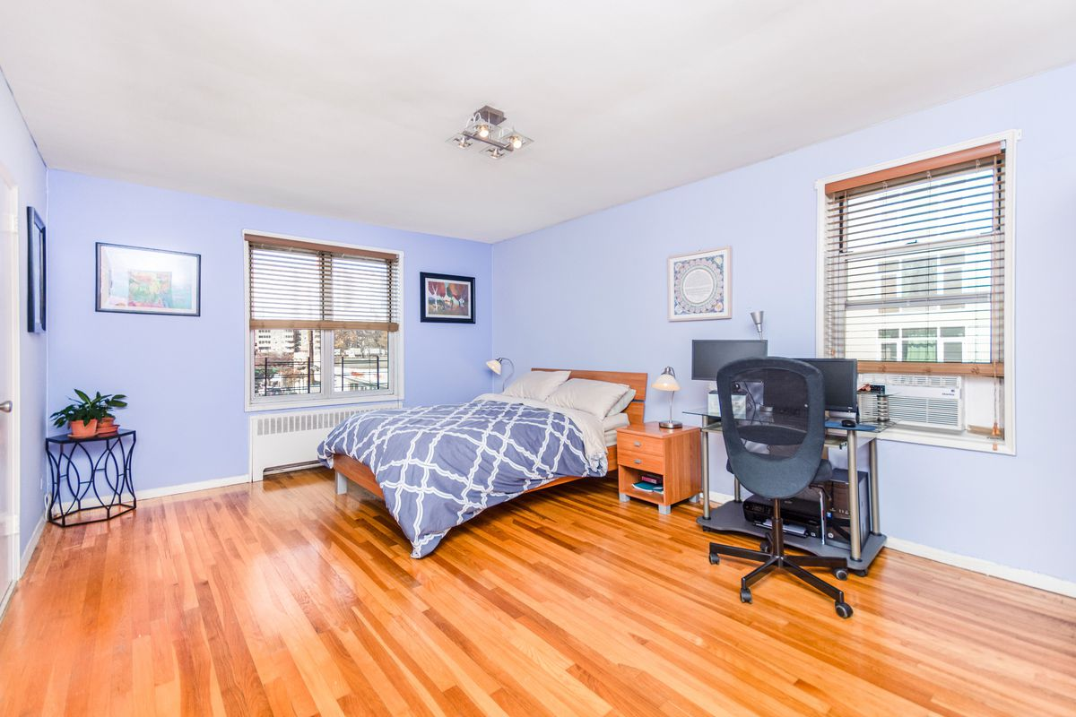 A bedroom with blue walls, hardwood floors, two windows, a desk with a computer, and a small bed.