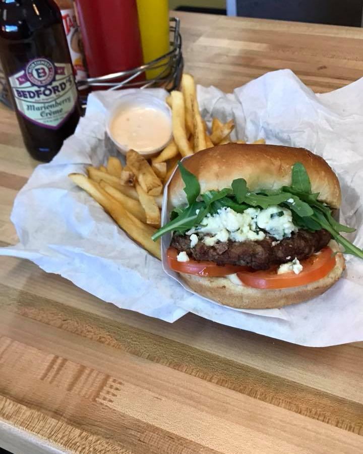 A burger at Zippy's, with lettuce, tomato, blue cheese, and a side of fries.