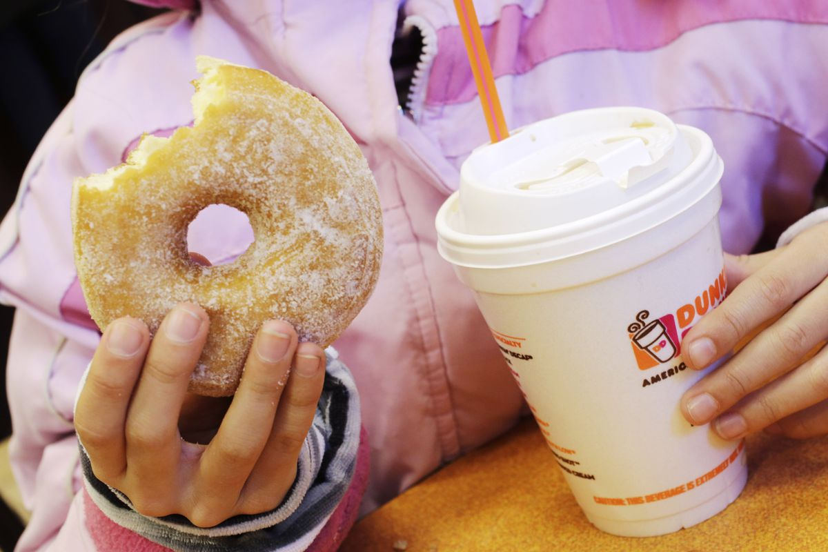 A person holding a donut with a bite taken out of it in one hand, and a styrofoam cup of dunkin donuts coffee in the other