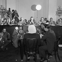 """FILE - In this Feb. 6, 1952 file photo, a masked former Polish soldier testifies on the 1940 Katyn Forest massacre to a house committee in Washington. Documents released Monday, Sept. 10, 2012 lend weight to the belief that suppression within the highest levels of the U.S. government helped cover up Soviet guilt in the killing of some 22,000 Polish officers and other prisoners in the Katyn forest and other locations in 1940. In a final report released in 1952, the committee declared there was no doubt of Soviet guilt, and called the massacre """"one of the most barbarous international crimes in world history."""" It found that Roosevelt's administration suppressed public knowledge of the crime, but said it was out of military necessity. It also recommended the government bring charges against the Soviets at an international tribunal - something never acted upon. Translator Roman Pucinski is at center right. On the rostrum are committee members, from left, Reps. Timothy Sheehan, R-Ill., Alvin E. O'Konski, R-Wis., George A. Dondero, R-Mich., Ray J. Madden, D-Ind., Daniel J. Flood, D-Pa., Foster Furcolo, D-Mass., and Thaddeus M. Machrowicz, D-Mich."""