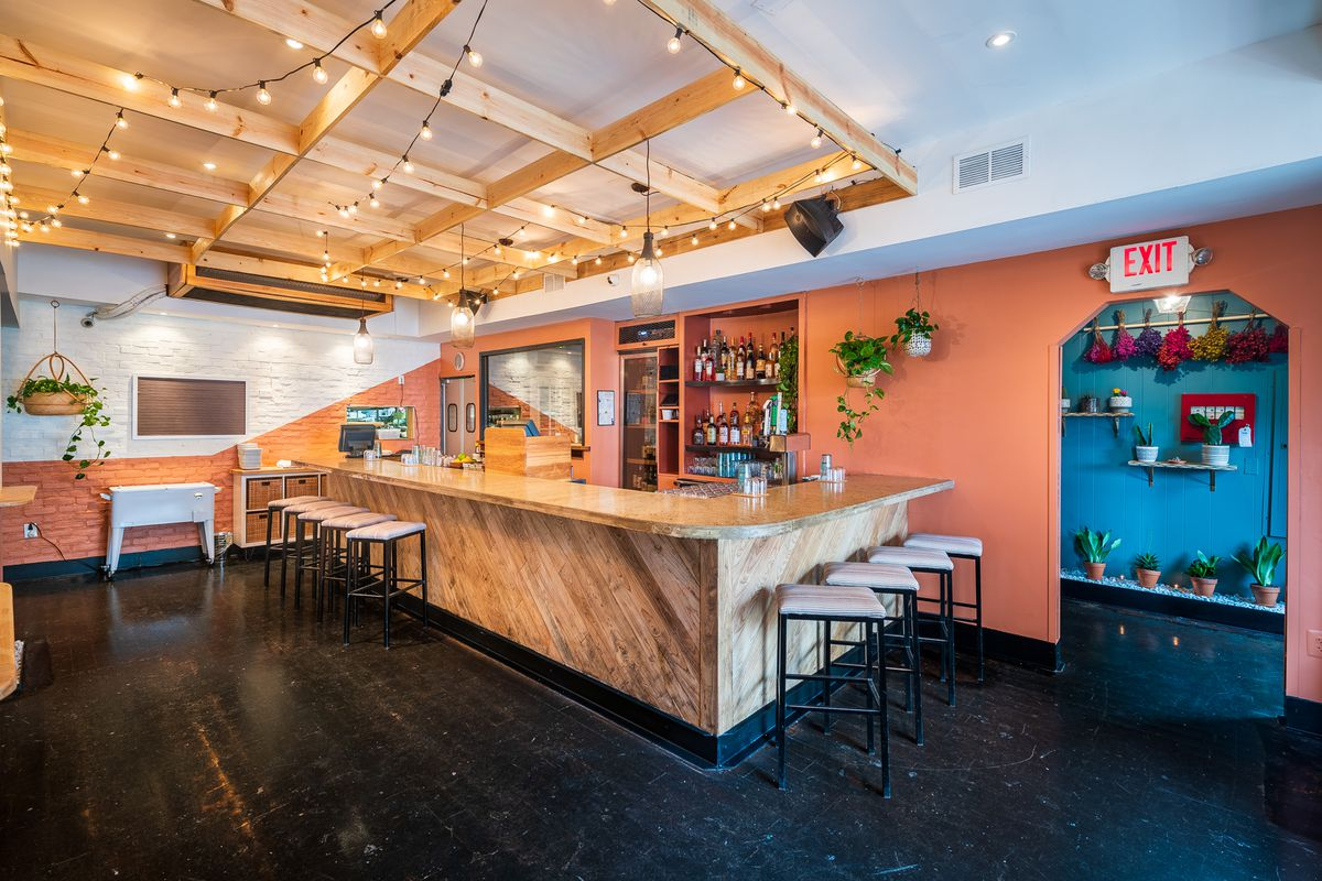 The light wood bar at Lulu's Winegarden is surrounded by walls covered in pinkish, terra cotta colored paint.