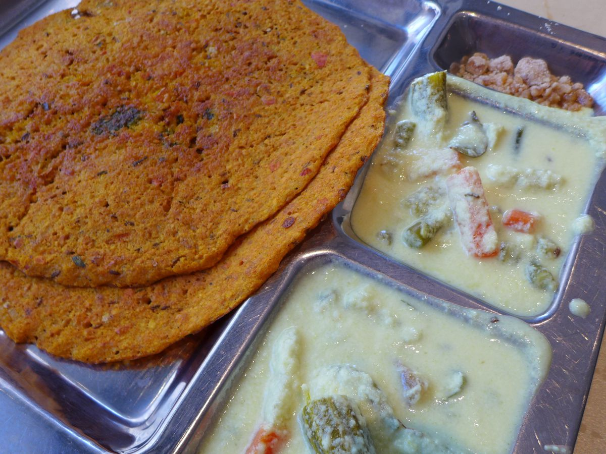 A metal tray with compartments containing a white vegetable curry and two red flatbreads.