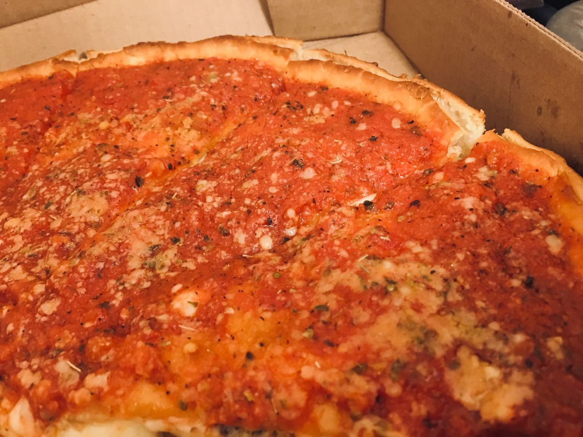 A red sauce topped Chicago-style deep dish pizza in a box.