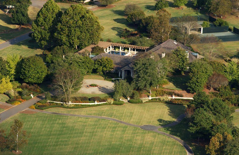 A massive mansion sits amid abundant trees and sprawling greens.