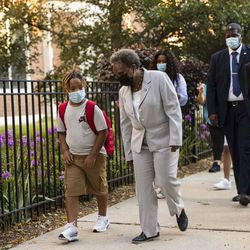 Mayor Lori Lightfoot walks with a student on the first day back to school at Mary E. Courtenay Language Arts Center.