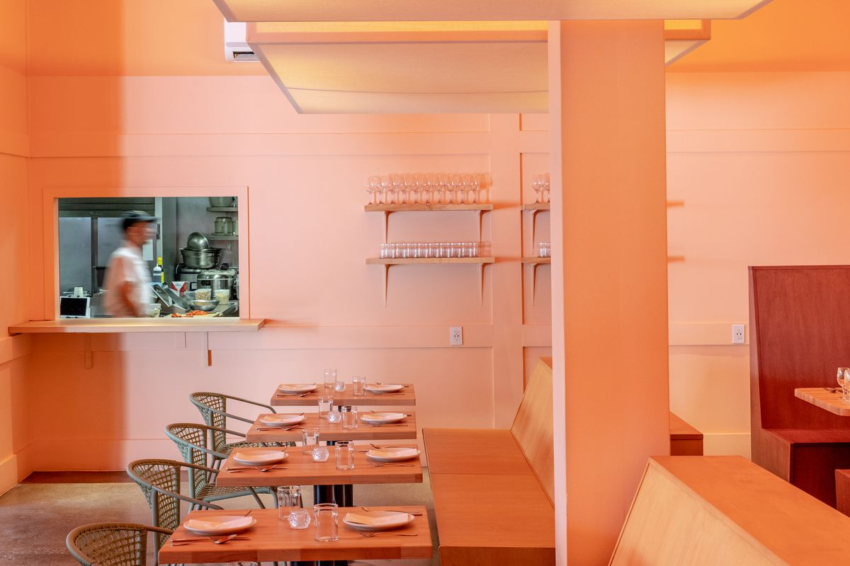 A light orange room for a new restaurant, with a view into the kitchen.