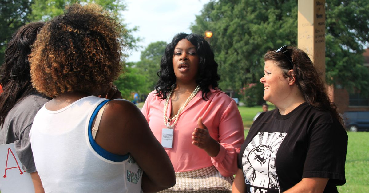 Shelby County Schools Board of Education member Stephanie Love (center) speaks with concerned teachers.