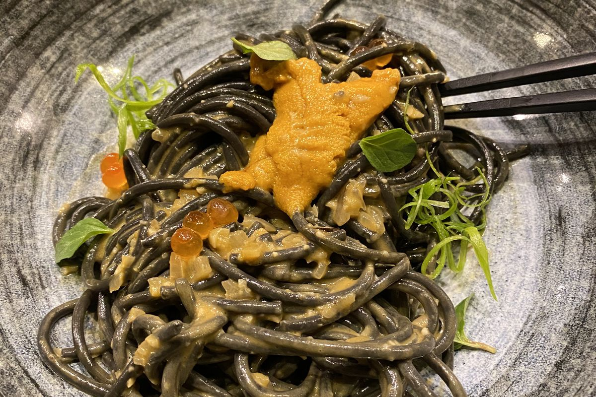 Squid ink pasta comes with a bright-orange uni butter with dots of salmon roe