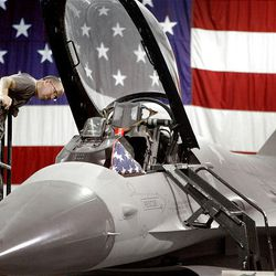 John Wade looks into the cockpit of an F-16 during Hill Aerospace Museum's annual Food for Life and Open Aircraft Day in Roy on Saturday. Visitors had the chance to look inside or walk through more than 25 of the nation's most historic planes.