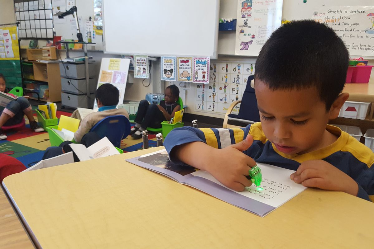 First graders at Paris Elementary in Aurora use toys and light pointers to help focus while reading individually.