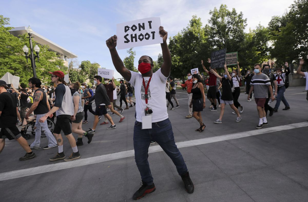 """Monte McElory holds a """"Don't Shoot"""" sign as he marches to the Salt Lake Public Safety Building in Salt Lake City on Monday, June 1, 2020. Recent protests against police brutality, racial discrimination and the killing of George Floyd turned violent in Salt Lake City and other cities across the nation, prompting Gov. Gary Herbert to call in the Utah National Guard."""