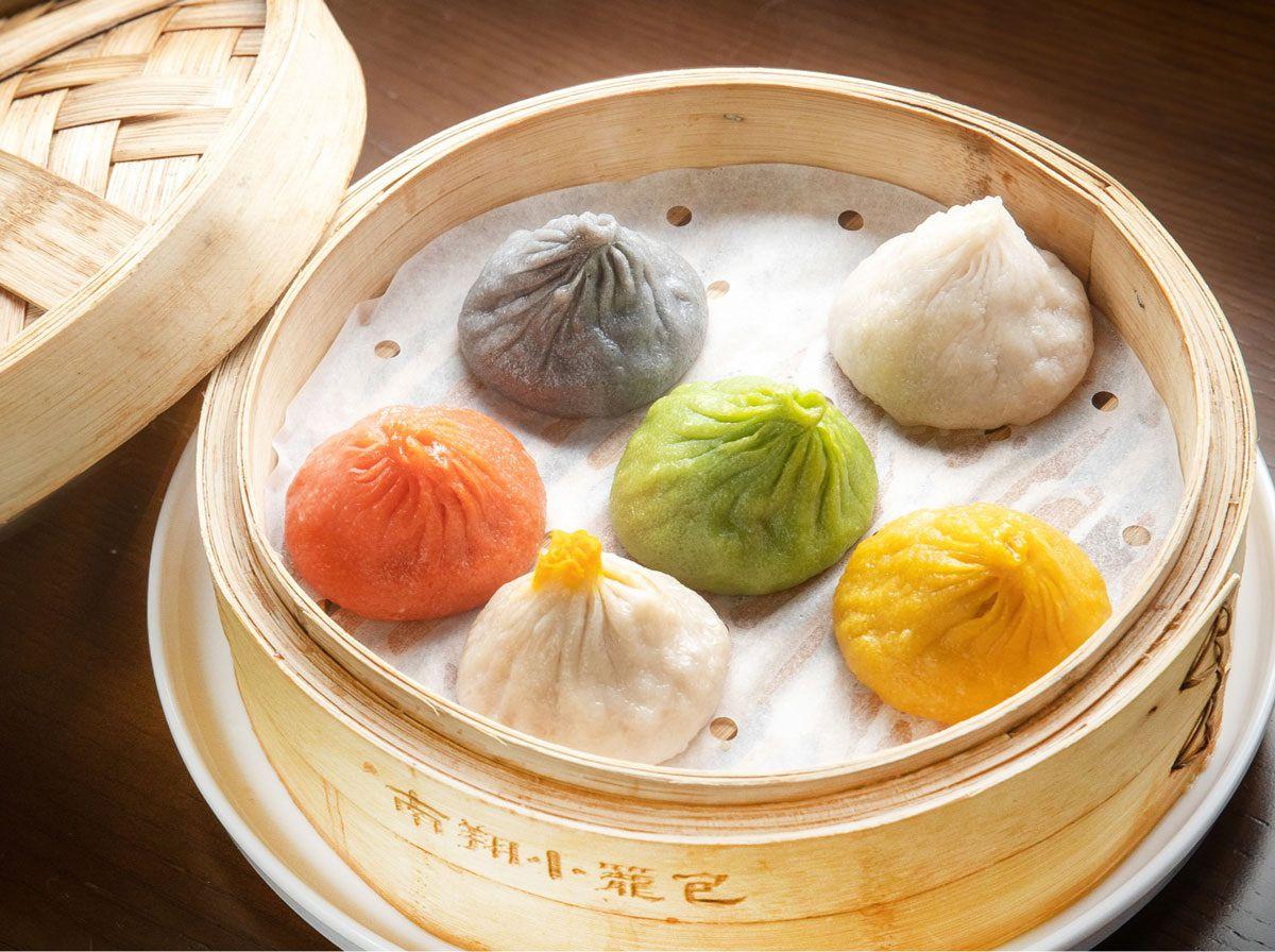 Colorful soup dumplings in a steamer.