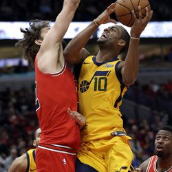 Chicago Bulls center Robin Lopez, left, guards Utah Jazz guard Alec Burks during the second half of an NBA basketball game Wednesday, Dec. 13, 2017, in Chicago. The Bulls won 103-100. (AP Photo/Nam Y. Huh)