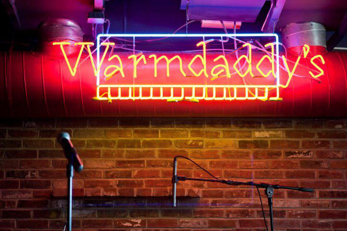 neon sign that says warmdaddy's on brick wall with microphone below