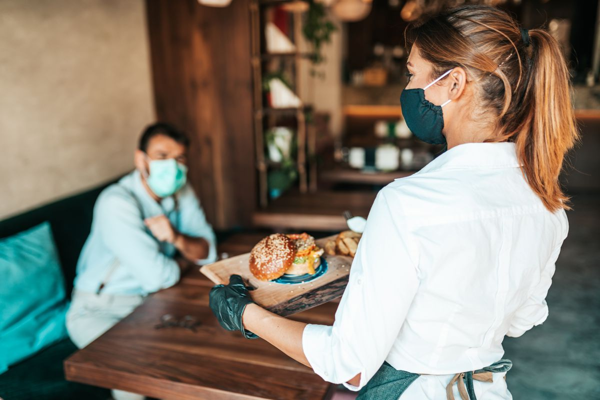 A masked serving brings a burger to a masked diner