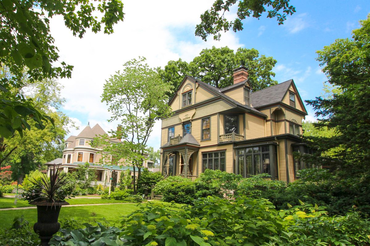 A light brown home in Chicago's Oak Park neighborhood with large green front yard and green shrubs.