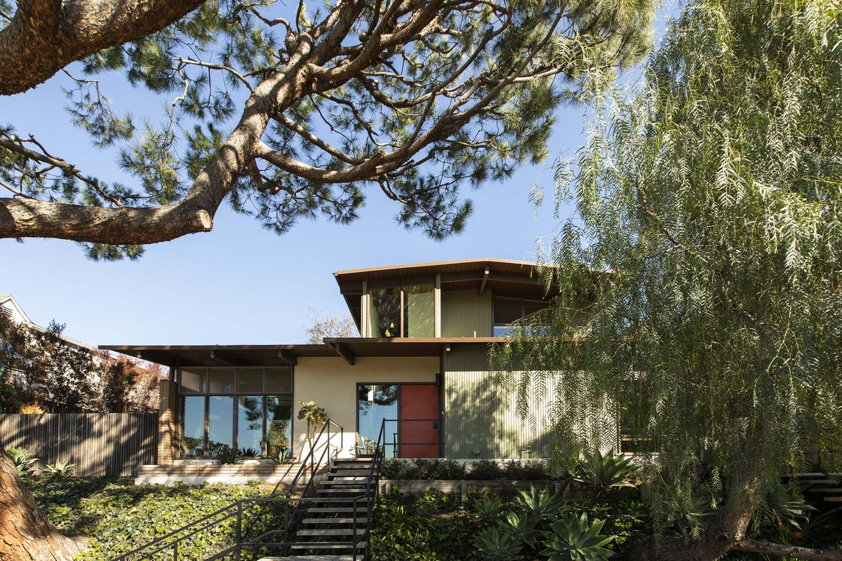 A midcentury modern style home has a bright red door with a staircase leading up to it. Two large trees in the foreground of the image frame the house.