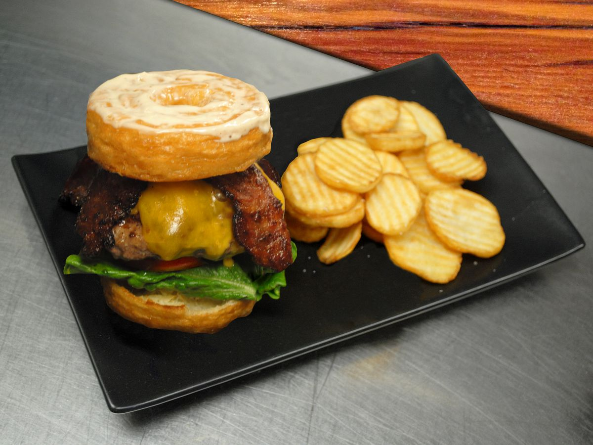 A towering elk burger atop a doughnut bun with crinkle cut french fries sits on a black plate. The dish is served at Bit Bar, an arcade game-filled restaurant in Salem, Massachusetts