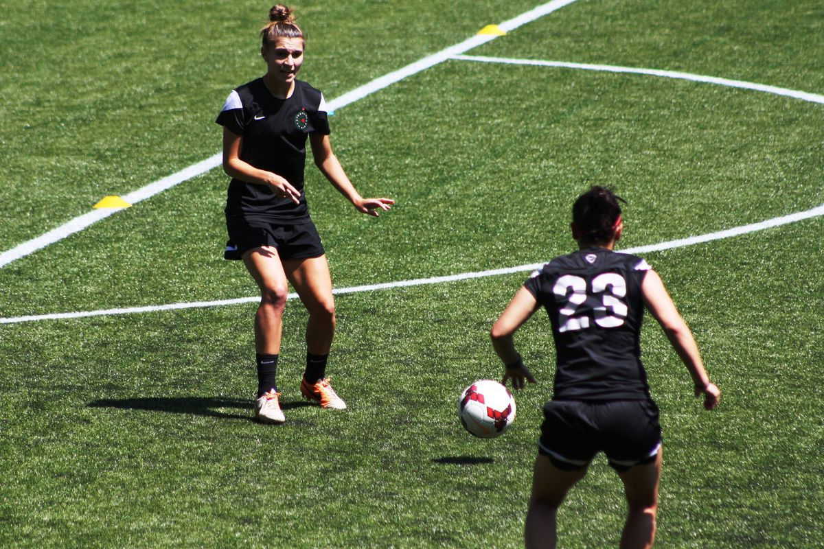 Thorns defender Stephanie Catley works with teammate Jackie Acevedo during training 6/2/2014.