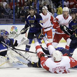 Detroit Red Wings' Pavel Datsyuk, front right, of Russia, slips as St. Louis Blues goalie Brian Elliott, left, deflects the puck during the first period of an NHL hockey game on Wednesday, April 4, 2012, in St. Louis.