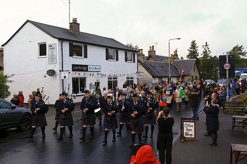 A parade of gab pipers goes through an old Scottish village.