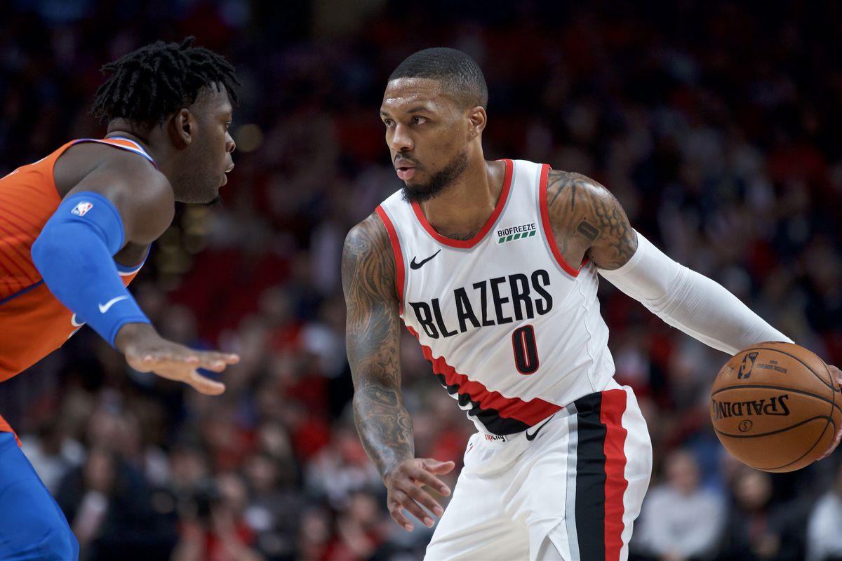 Portland Trail Blazers guard Damian Lillard dribbles around Oklahoma City Thunder guard Luguentz Dort during the first quarter at the Moda Center.