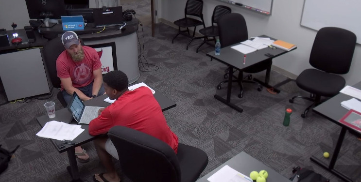 Ryan FitzPatrick at a desk wearing a Yeti Coolers hat