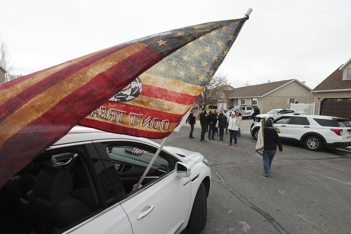 People fly an American flag at a protest against masks.
