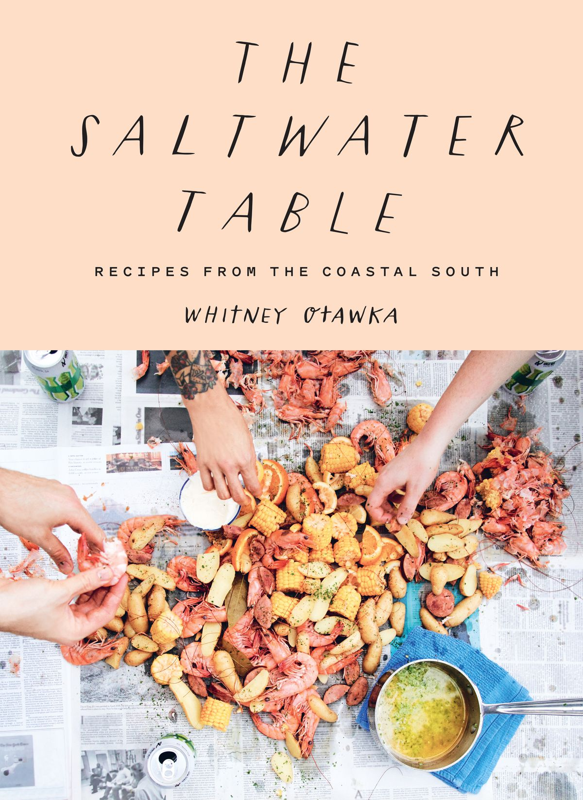 """Cover of """"The Saltwater Table,"""" with soft pink coloring and photo of hands reaching for seafood on a newspaper-covered table, with cans of beer open alongside them"""