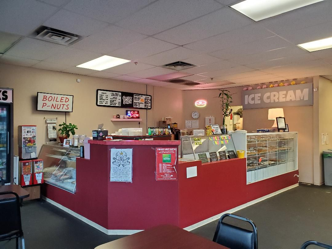 A view of the interior of Good Day Donuts, with a red counter, a display case, and an ice cream sign to the far right.