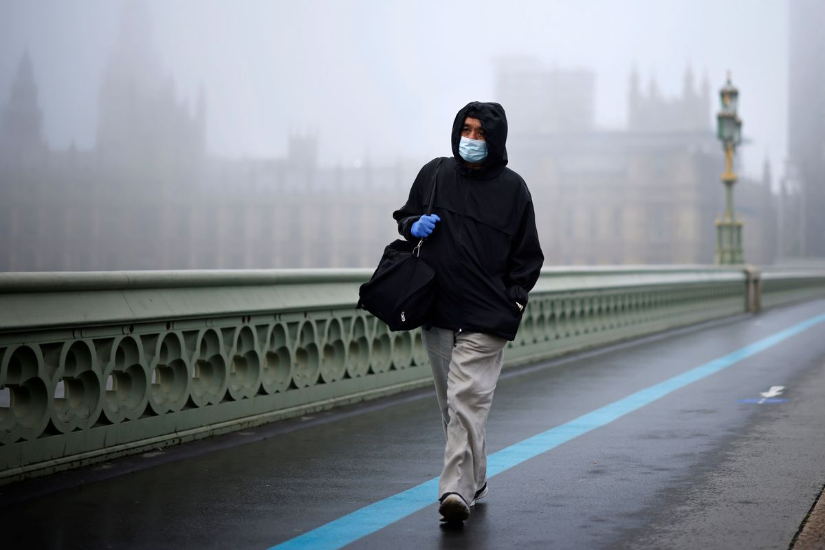 A man in tan slacks, a black hoodie, and a blue surgical mask walks past the green wrought iron that makes up the side of Westminster Bridge. Behind him, in heavy fog, are the stone peaks of the Parliament building.