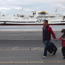 Ships remain in dock, as a man and child walk in port during a 48-hours strike at the port of Piraeus, near Athens, on Tuesday, April 10, 2012. Ferry services to Greek islands have been halted by a 48-hour strike that is expected to hit the start of the country's tourism season and celebrations for Orthodox Easter this Sunday.