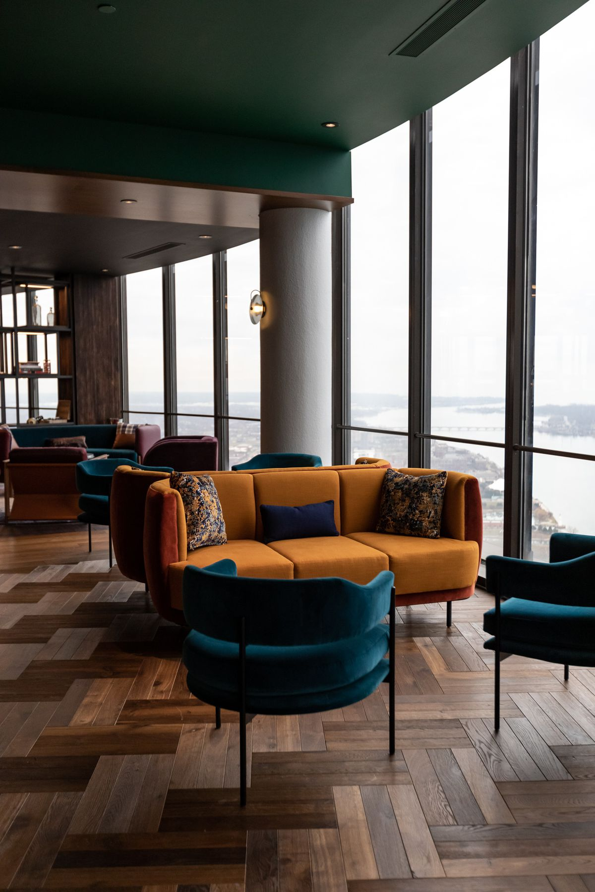 Jewel-toned velvet chairs and sofas on patterned wood floors in the lounge next to windows looking out towards St. Clair Shores.