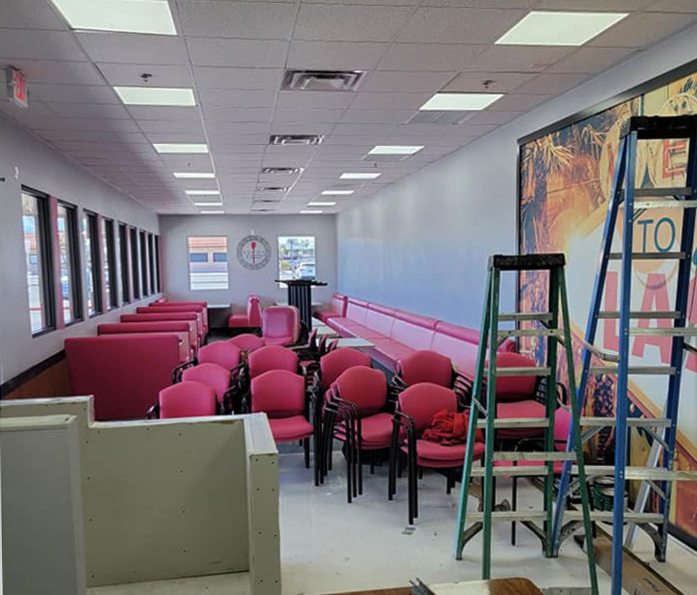 Construction of the dining room at the new Vickie's Diner location, with pink vinyl seating and a large Las Vegas mural.