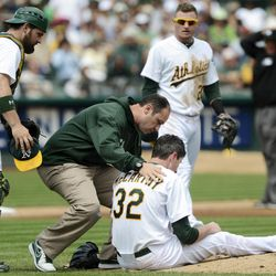 Oakland Athletics pitcher Brandon McCarthy (32) is tended to by a trainer after being struck in the head by a ball hit by Los Angeles Angels' Erick Aybar in the fourth inning of a baseball game, Wednesday, Sept. 5, 2012, in Oakland, Calif. McCarthy was sent to the hospital, and according to the team he never lost consciousness. The Angels won 7-1.