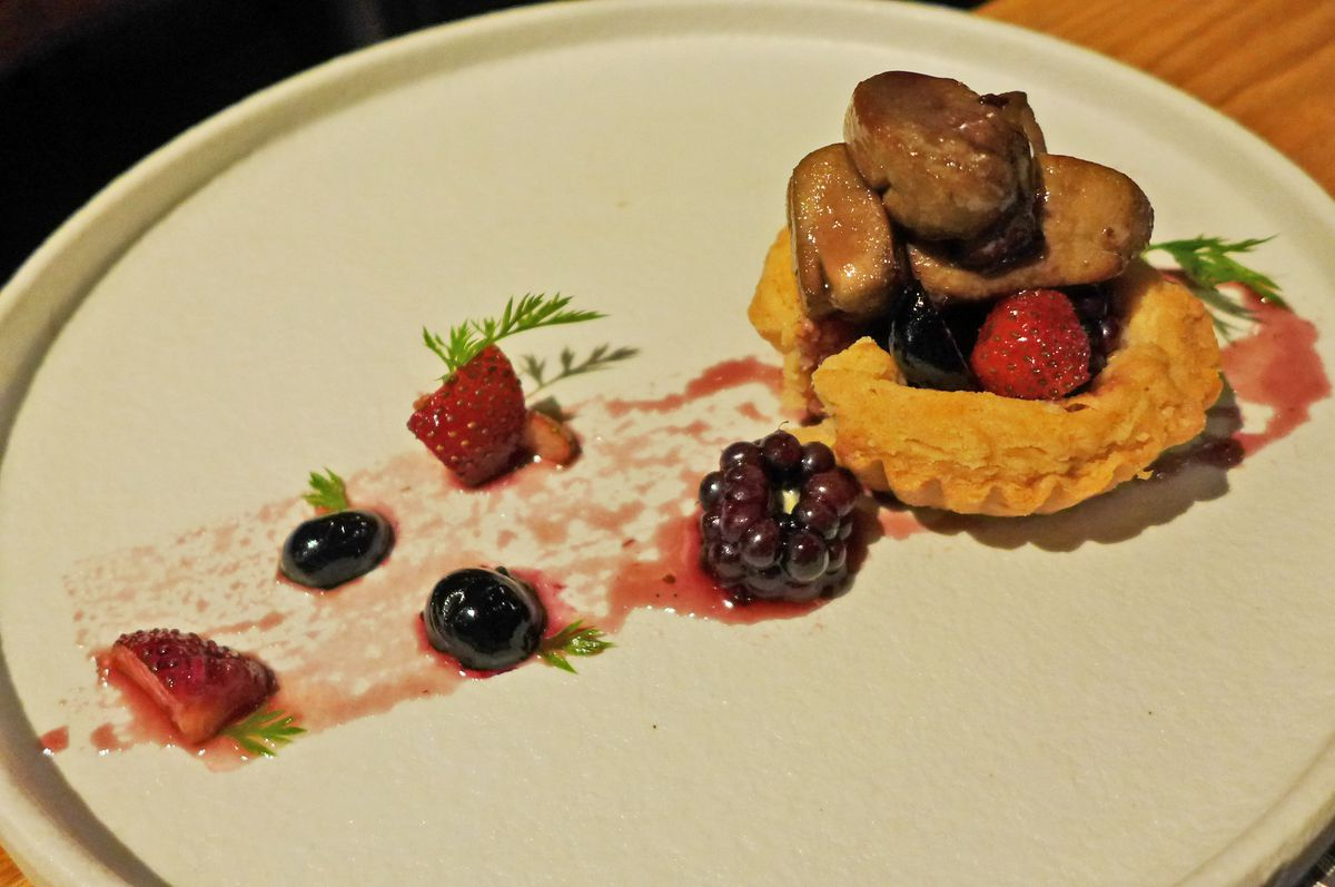 A line of strewn berries runs up to a pastry shell with lobes of foie gras inside...