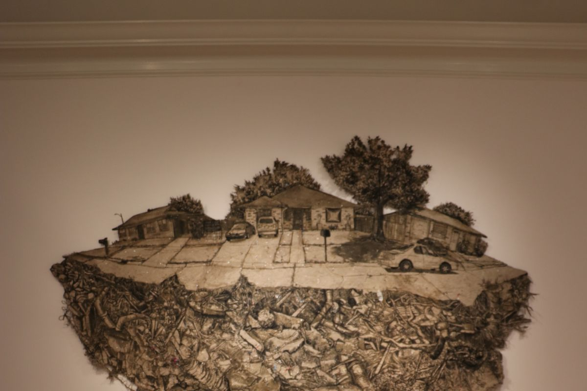 A handmade, irregularly sized piece of paper printed with images of a neighborhood atop a landfill hangs on a museum wall