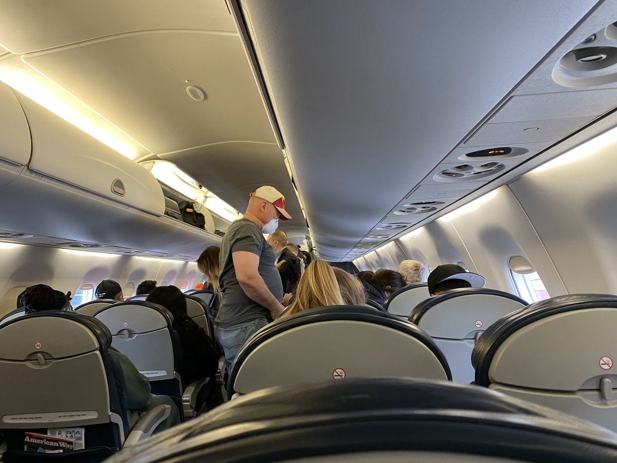 A masked man stands up in a semi-crowded plane cabin.
